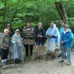 Group of Retired Seniors in Rain Gear Pose for a Photo Next to a New Hampshire Trail Head